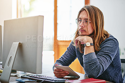 Buy stock photo Shot of a focused young man sitting at his desk in an office working on a computer