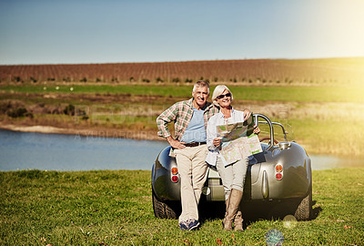 Buy stock photo Shot of a happy senior couple posing next to a convertible while out on a roadtrip