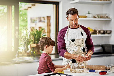 Buy stock photo Shot of a father and son baking biscuits in the kitchen