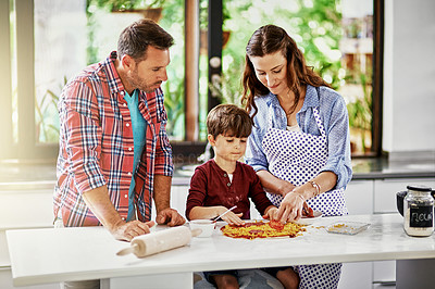 Buy stock photo Shot of a young family making pizza together