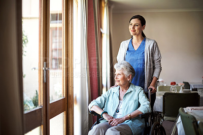 Buy stock photo Shot of a young nurse caring for a senior woman in a retirement home