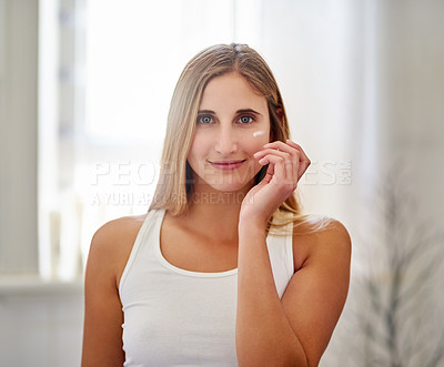 Buy stock photo Portrait of a beautiful young woman applying moisturizer to her face in the bathroom at home