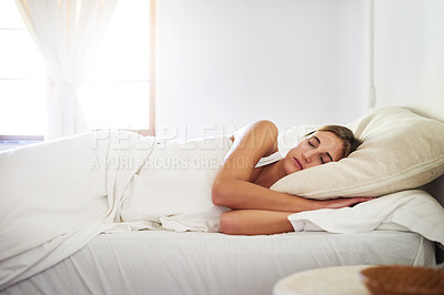 Buy stock photo Shot of a serene young woman sleeping in her bed at home