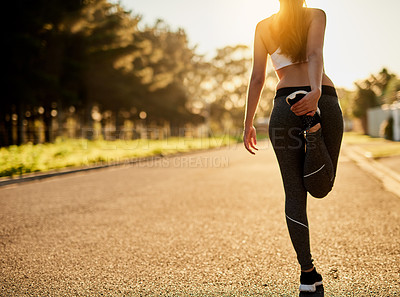 Buy stock photo Rearview shot of an unidentifiable young woman stretching before a run