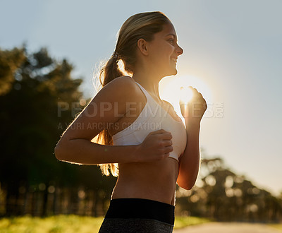 Buy stock photo Shot of a happy young woman out for a run in nature