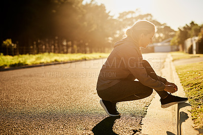 Buy stock photo Shot of a young woman tying her shoelace before going on a run