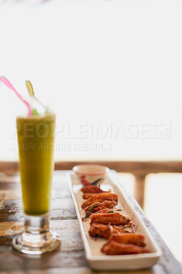 Buy stock photo Shot of chicken wings and a shake sitting on a table in an oceanside restaurant in Thailand
