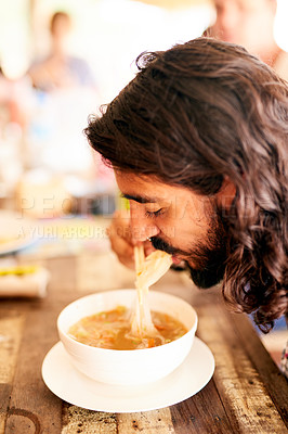 Buy stock photo Shot of a young man eating a bowl of noodles in a restaurant in Thailand
