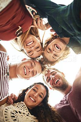 Buy stock photo Low angle portrait of a group of friends standing in a huddle on the beach
