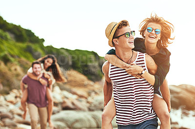 Buy stock photo Cropped shot of two affectionate young couples enjoying their time on the beach