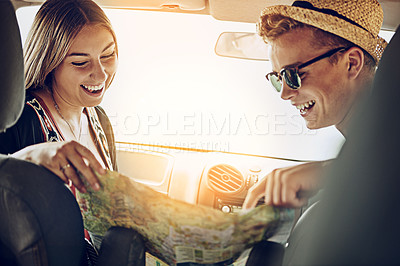 Buy stock photo Cropped shot of a young couple reading a map while on a roadtrip together