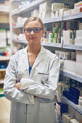 Buy stock photo Portrait of a pharmacist standing in a isle with her colleague working in the background