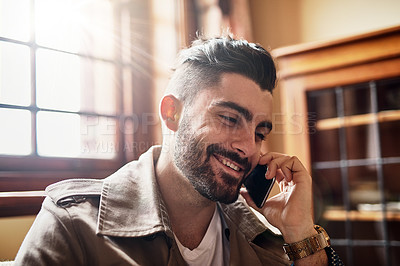 Buy stock photo Shot of a handsome young man smiling and talking on a cellphone at home