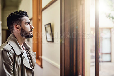 Buy stock photo Shot of a handsome young man standing by a window looking deep in thought