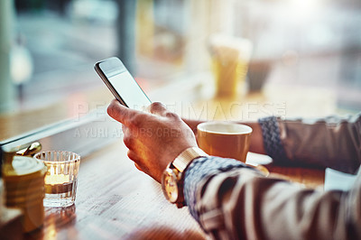 Buy stock photo Cropped closeup shot of a young man reading a text message while sitting at a counter in a cafe