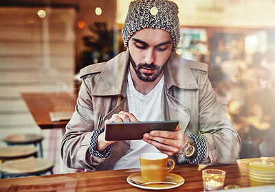 Buy stock photo hot of handsome young man using a digital tablet while sitting at a counter in a cafe