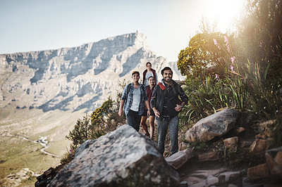 Buy stock photo Full length shot of a group of friends walking along a mountain trail