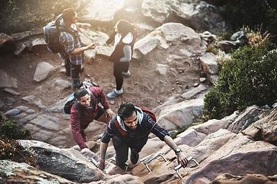 Buy stock photo Shot of a group of friends climbing a ladder while hiking in the mountains