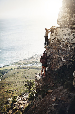 Buy stock photo Shot of a group of friends scaling the side of a mountain while out for a hike