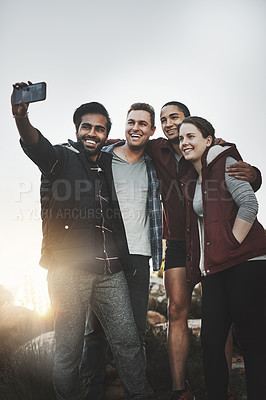 Buy stock photo Shot of a group of friends taking selfies while hiking together in the mountains