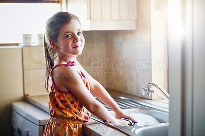 Buy stock photo Portrait of a little girl washing dishes at home