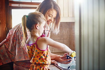 Buy stock photo Cropped shot of a mother and her little daughter washing dishes together at home