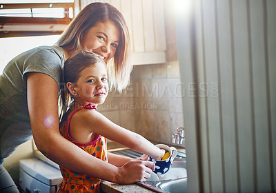 Buy stock photo Portrait of a mother and her little daughter washing dishes together at home
