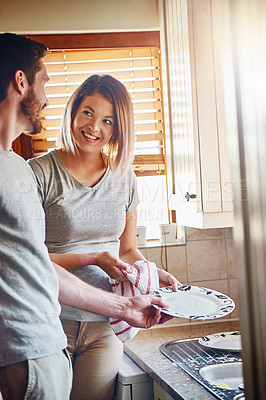 Buy stock photo Cropped shot of a young couple washing dishes together at home