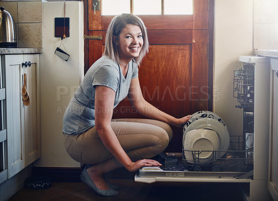 Buy stock photo Portrait of a young woman using a dishwashing machine at home