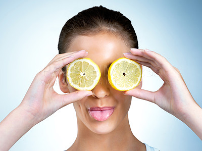 Buy stock photo Shot of a health-conscious young woman posing with lemons over her eyes in studio