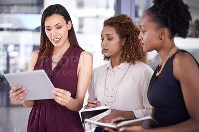 Buy stock photo Cropped shot of three businesswomen discussing something in the office