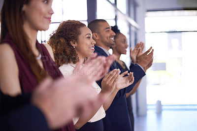 Buy stock photo Closeup shot of a group of businesspeople clapping while standing in a row in an office