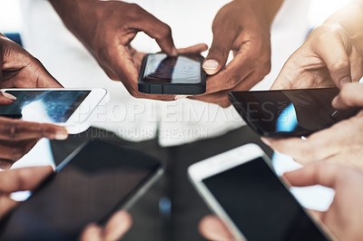 Buy stock photo Cropped shot of a group of people using their smart phones in synchronicity
