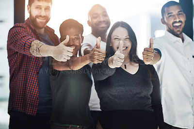 Buy stock photo Portrait of a team of happy colleagues showing thumbs up in a modern office