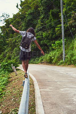 Buy stock photo Rearview shot of an unidentifiable young man exploring an exotic destination alone