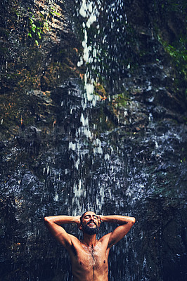 Buy stock photo Shot of a happy young tourist standing under a waterfall in the jungle