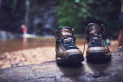 Buy stock photo Shot of a pair of empty shoes standing on a log by a river in a jungle