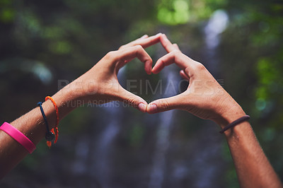 Buy stock photo Shot of an unidentifiable young woman making a heart gesture with her hands in the jungle