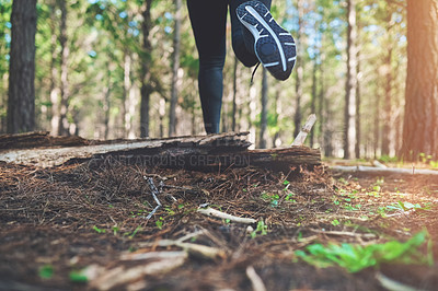 Buy stock photo Cropped shot of an unrecognizable young woman out for a jog in the woods