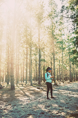 Buy stock photo Full length shot of an athletic young woman sending a text while jogging in the woods