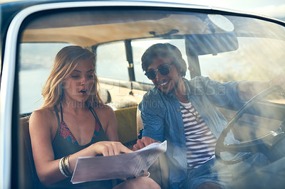 Buy stock photo Cropped shot of an affectionate young couple looking at a map during their roadtrip