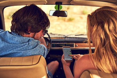 Buy stock photo Rearview shot of an affectionate young couple following their gps during a roadtrip