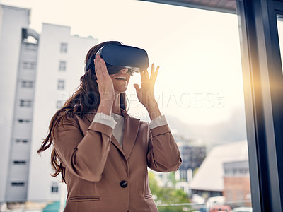Buy stock photo Shot of a young businesswoman wearing a VR headset in an office