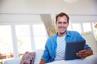 Buy stock photo Portrait of a man using a digital tablet and relaxing on the sofa at home