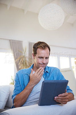 Buy stock photo Shot of a man looking uncertain while using a digital tablet at home