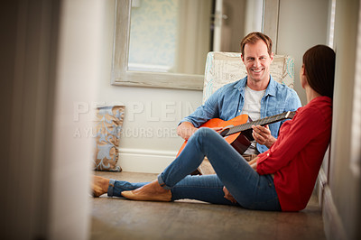 Buy stock photo Shot of a man playing the guitar for his wife at home