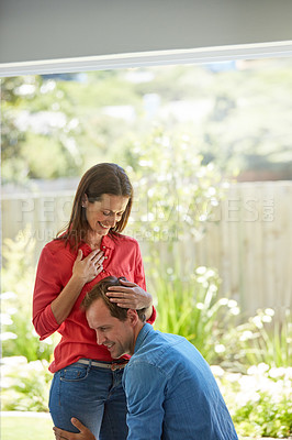 Buy stock photo Shot of a man pressing his ear to his wife's pregnant stomach at home