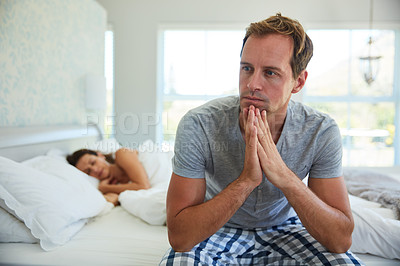 Buy stock photo Shot of a man looking worried while his wife sleeps in the background