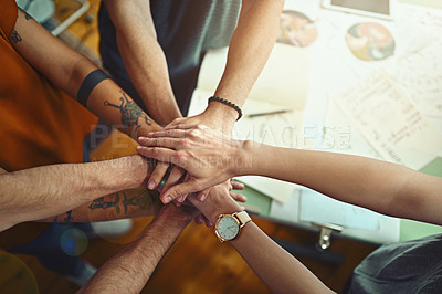 Buy stock photo High angle shot of a group of young designers standing with their hands in a huddle