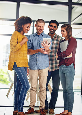 Buy stock photo Shot of a team of designers working together on a digital tablet in an office